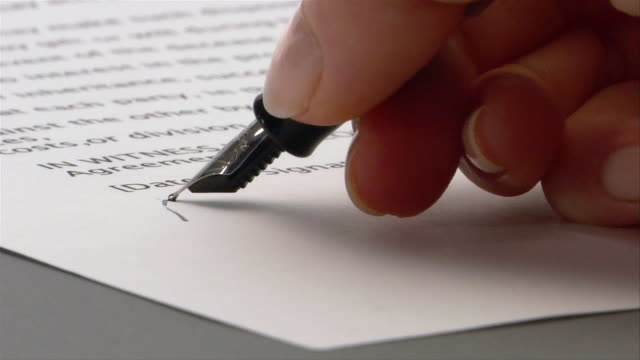 Close up woman signing document