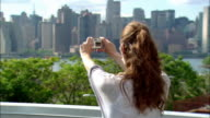 Close up woman taking digital video of skyline / turning around and smiling at camera