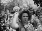 B/W 1955 close up woman throwing knives outdoors / crowd of girls watching in background