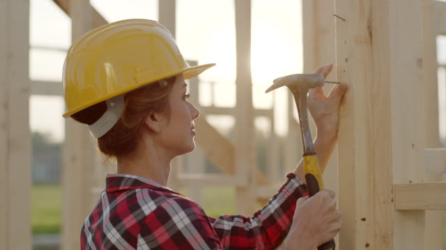 Close up, woman using hammer to stuck nail in to the wood