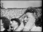 B/W 1951 close up woman with mouth open putting hands on face in horror in audience at boxing match / Berlin