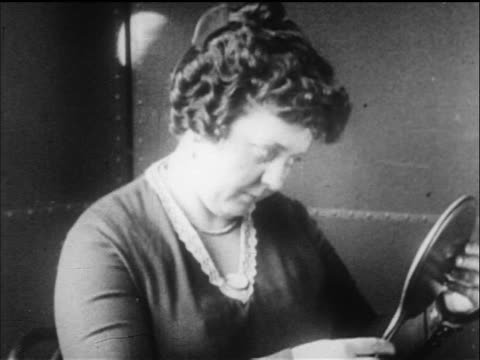 B/W 1919 close up woman with permanent wave looking in hand mirror in beauty parlor / newsreel
