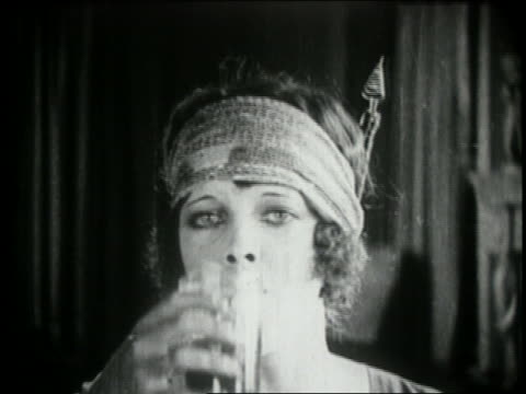 B/W 1924 close up woman with scarf on head takes sip of drink + makes face