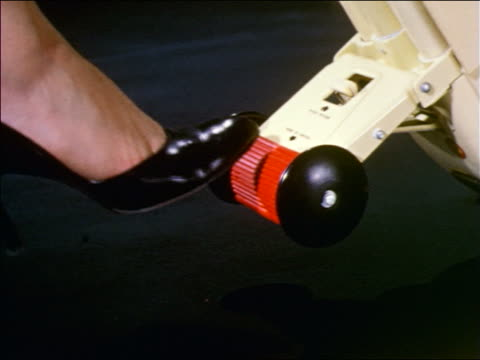 1959 close up woman's foot pressing button on floor polisher / industrial