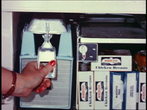 1958 close up woman's hand ejecting ice cubes from ice cube tray into ice container in open freezer