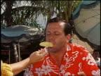1960 close up woman's hand feeding pineapple to nodding man in Hawaiian shirt outdoors / Hawaii