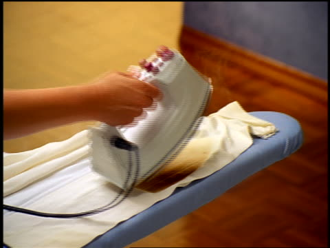 close up woman's hand lifting iron to reveal burned shirt on ironing board