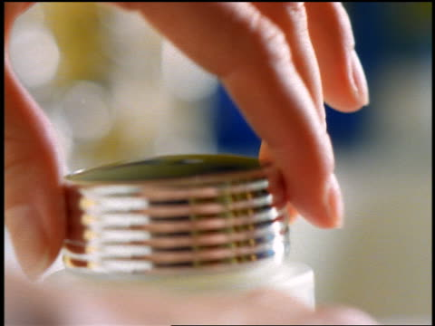 close up woman's hand lifting lid from jar of skin lotion/cream + dipping finger in