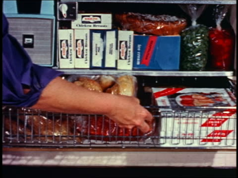 1958 close up woman's hand opening metallic basket filled with food in open freezer