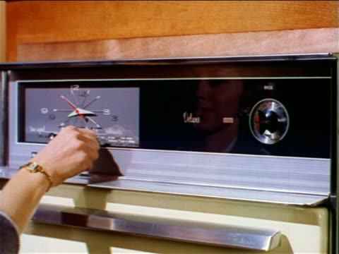 1962 close up woman's hand setting timer + turning knob on oven / her reflection in glass / industrial