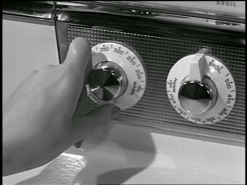 B/W close up woman's hand turning knob on oven