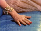1955 close up woman's hand with bracelet rubbing seat of car / industrial