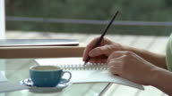 Close up woman's hand writing in journal at desk