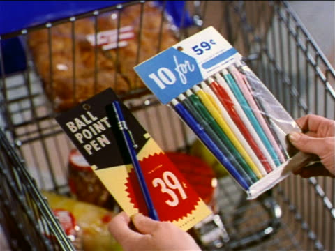 1962 close up woman's hands holding two packages of ball point pens over shopping cart