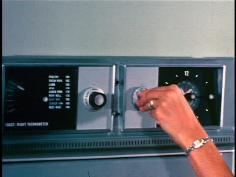 1950 close up woman's hands turning knobs on oven + setting timer