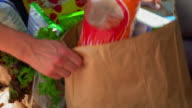 close up PAN woman's hands unloading groceries from trunk + handing them to children