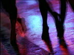 close up women's feet in high heels walking in street at night