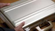 Close up wooden table/ briefcase sliding across/ man's hands open case, revealing bundles of $20 bills