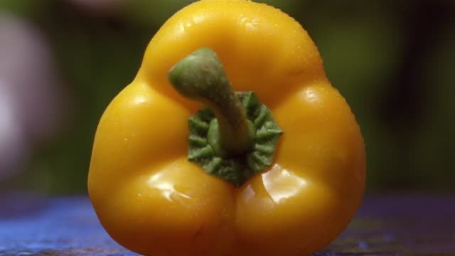 Close up yellow pepper being cut in half