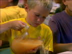 close up young blond boy pouring orange juice at table with other children in camp mess hall