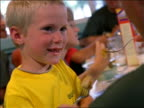 close up young blonde boy eating + smiling at table with others in camp mess hall / hand trying to feed him