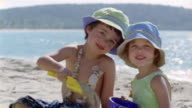 Close up young boy and girl playing with shovel and pail on the beach