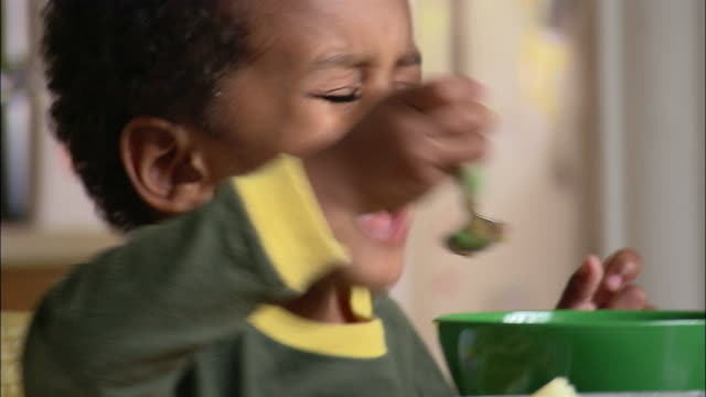 Close up young boy eating cereal at breakfast table