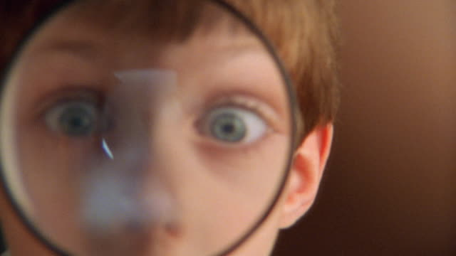 Close up young boy looking through magnifying glass and making faces