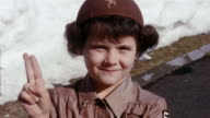 1960 close up young girl in Brownie uniform smiling at CAM and making Girl Scout hand sign