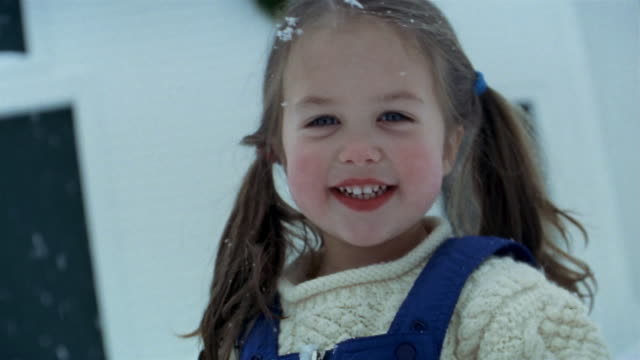 Close up young girl smiling at CAM in snow
