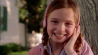 Close up young girl w/headphones bouncing to music outdoors