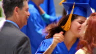 close up young Hispanic woman wearing cap + gown crying + hugging parents outdoors / Florida