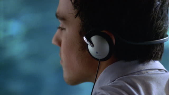 Close up young man listening to music on headphones by swimming pool / taking off headphones / Encino, CA
