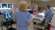 Close up zoom in pan nurse's back /medium shot nurse walking to doctor examining male patient in bed / PAN nurse walking