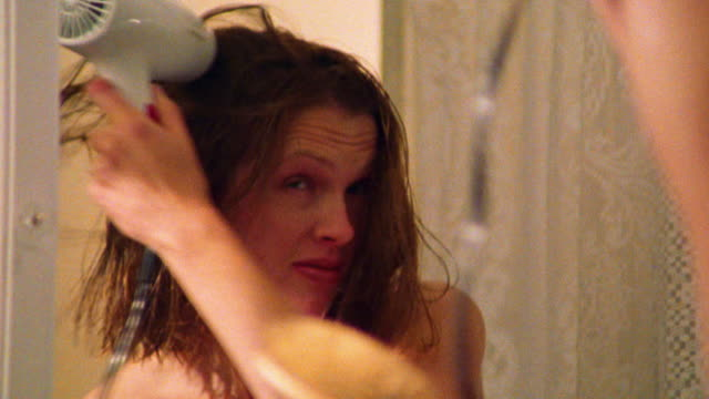close up zoom in reflection in mirror of woman blow drying hair after shower in bathroom