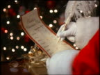 close up zoom in Santa Claus' gloved hand checking off Christmas list with feathered pen