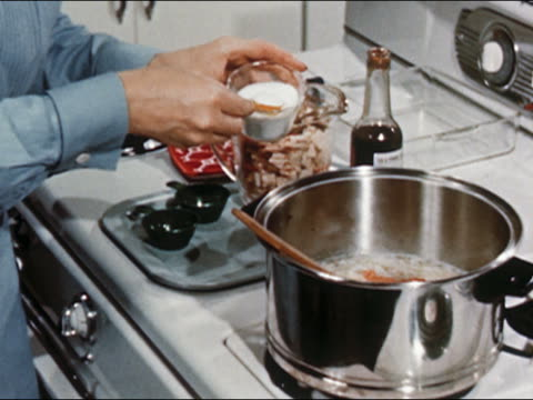 1951 Close up zoom in woman stirring chopped turkey, rice, and vegetables in pot on stove / AUDIO