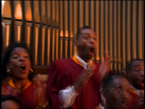close up PAN zoom in + zoom out Black gospel choir in robes singing + clapping in church
