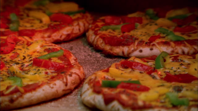 Close up zoom out from four time lapse pizza pies baking in oven