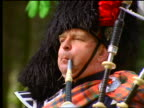 close up + zoom out man playing bagpipes near green forest / Callander, Scotland