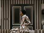 1971 close up zoom out model sitting on striped chair and spinning around / walking towards CAM in argyle ensemble