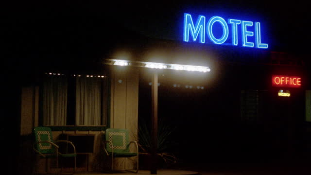 Close up zoom out neon motel and office sign at night