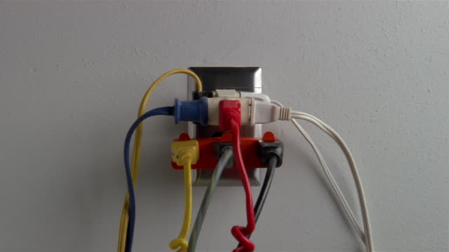 Close up zoom out wall outlet overflowing with 8 plugs