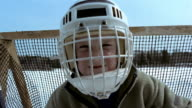 Close up zoom out young boy wearing goalie mask and standing in front of hockey goal / making faces