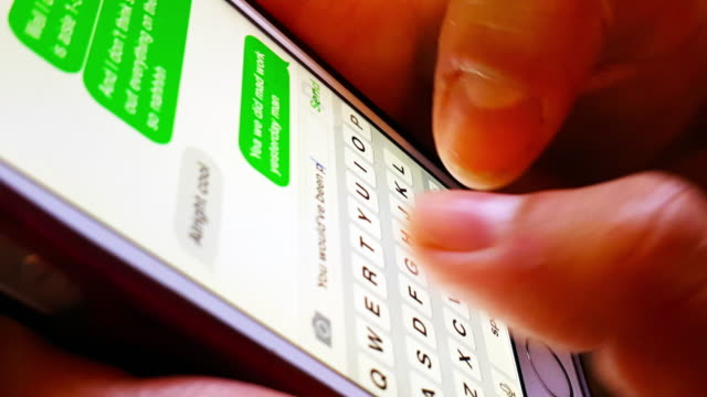 Close ups of girl's hands text message using smartphone