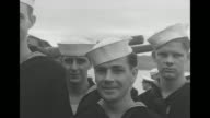 Close view of US and British sailors standing around and talking / two AfricanAmerican USN Petty Officers stand with British and US sailors / US and...