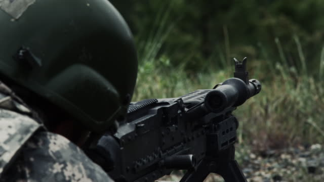 Close view over the shoulder of a soldier as he shoots a belt-fed machine gun.