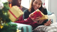 Close-up Asian Friendship Giving Christmas gifts in living room