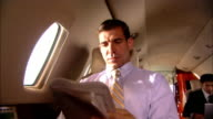 Close-up Businessman reading newspaper on private jet/ Miami, Florida, USA