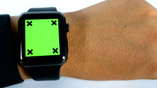 Close-up businessman using smart watch with green screen on white background, chroma key